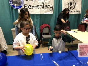 students at science fair doing experiment.